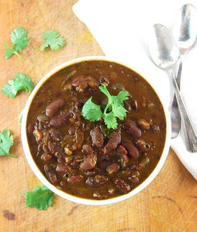 Rajma, Indian kidney beans curry in a white bowl with cilantro and two spoons and a white napkin