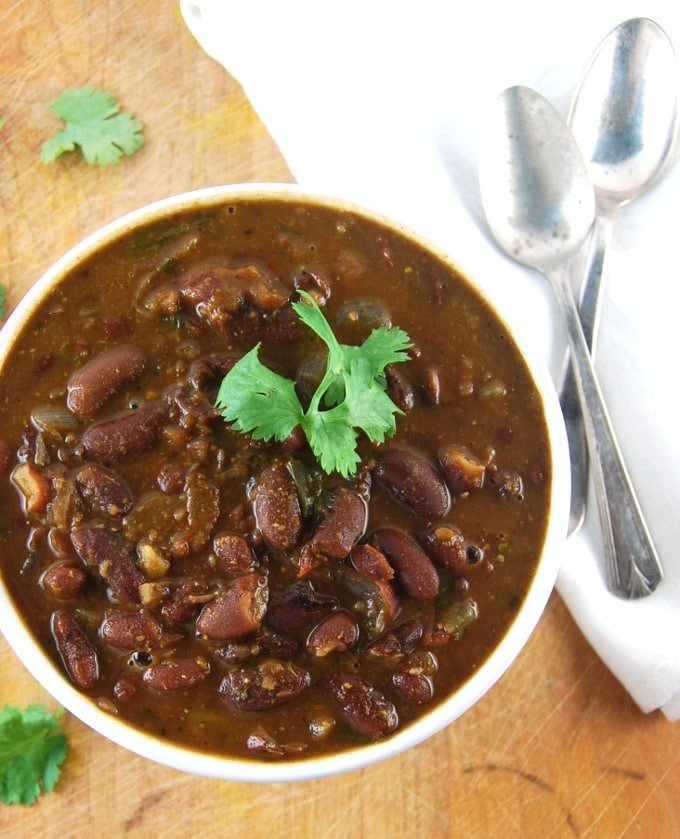 Rajma, Indian kidney beans in a tomato onion sauce, in a white ceramic bowl with a cilantro garnish. Next to it are two crisscrossed spoons, a white napkin on a wood background