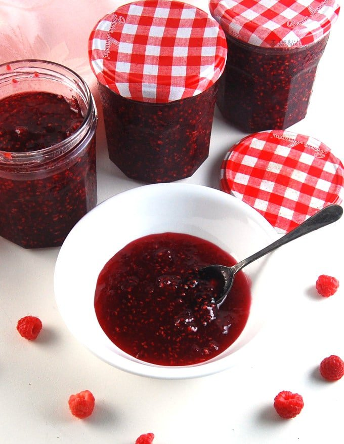 Raspberry Jam in a bowl with more jars of jam in the background and a few berries scattered around.