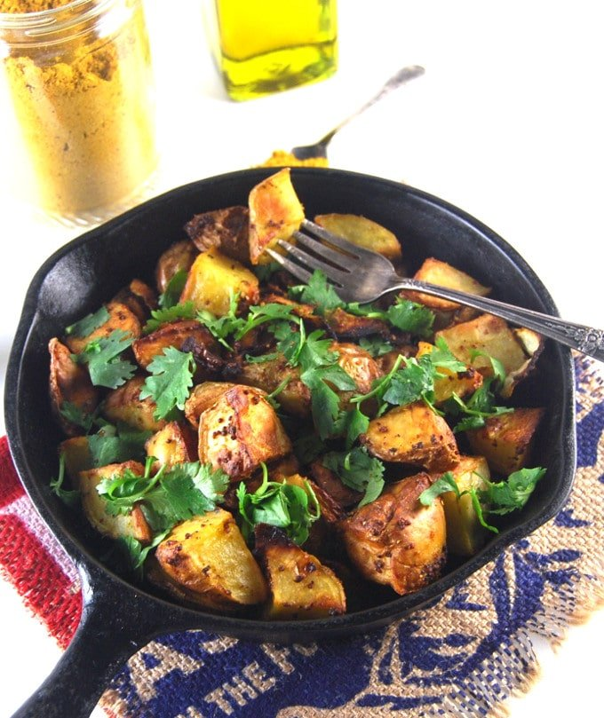 Golden Roasted Curry Mustard Potatoes in a cast iron skillet with a fork and curry powder in background.