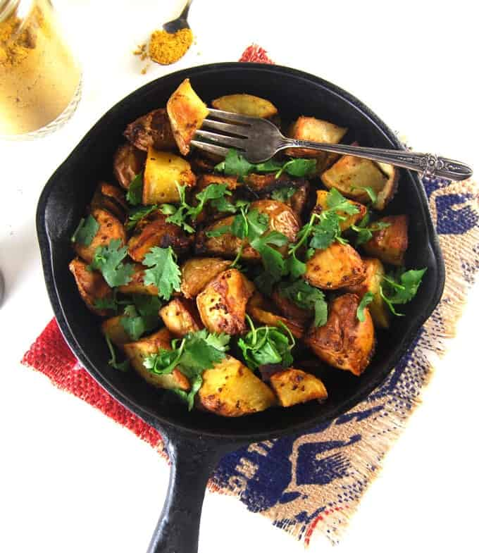 Golden Roasted Curry Mustard Potatoes. Overhead shot of the potatoes in a cast iron pan with a fork.