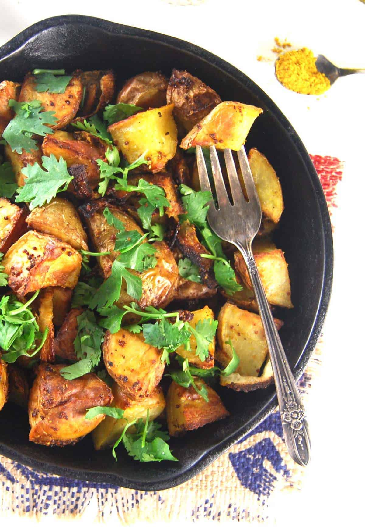 Golden Roasted Curry Mustard Potatoes in a cast iron pan with fork and curry powder in a spoon.