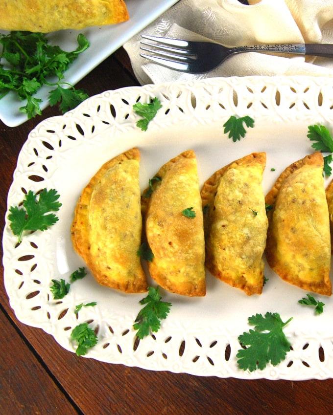 Four keema samosas visible on a white platter with cilantro garnish.