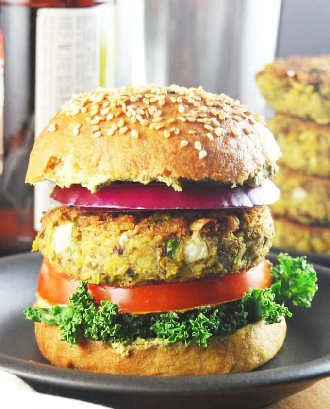 Photo of a sprouted mung bean burger with kale, tomato, onion on a whole wheat hamburger bun with more burger patties in the background.