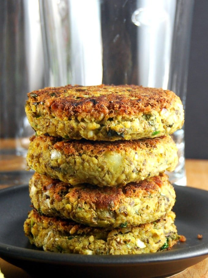 Photo of stacked vegan mung bean burger patties on a  black plate.