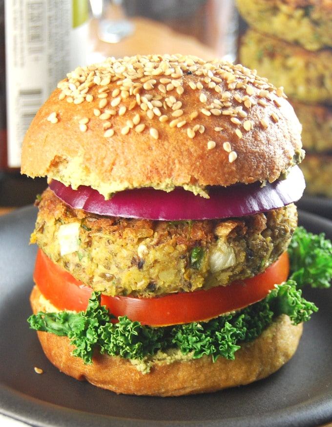 Photo of a sprouted mung bean burger with kale, tomato, onion on a whole wheat hamburger bun.