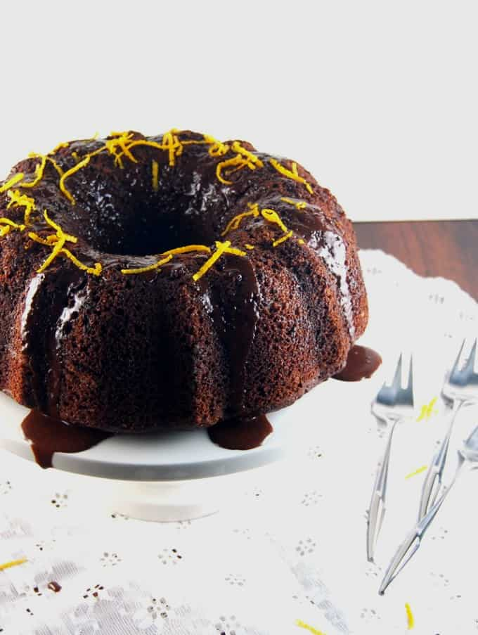 Photo of Vegan Chocolate Orange Bundt Cake on a cake stand on a lace tablecloth with forks.