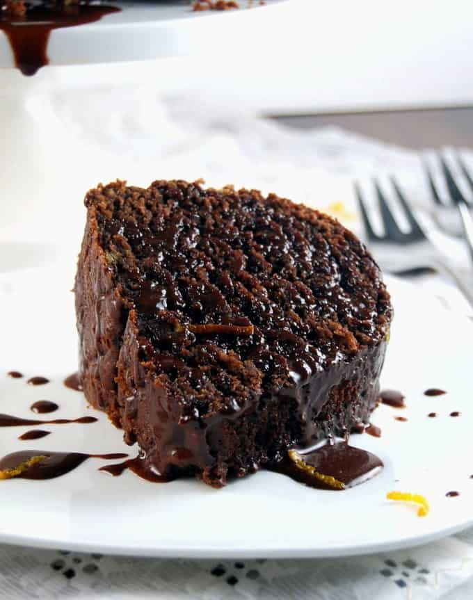 Photo of a slice of vegan chocolate orange bundt cake with chocolate sauce poured over on a white plate.