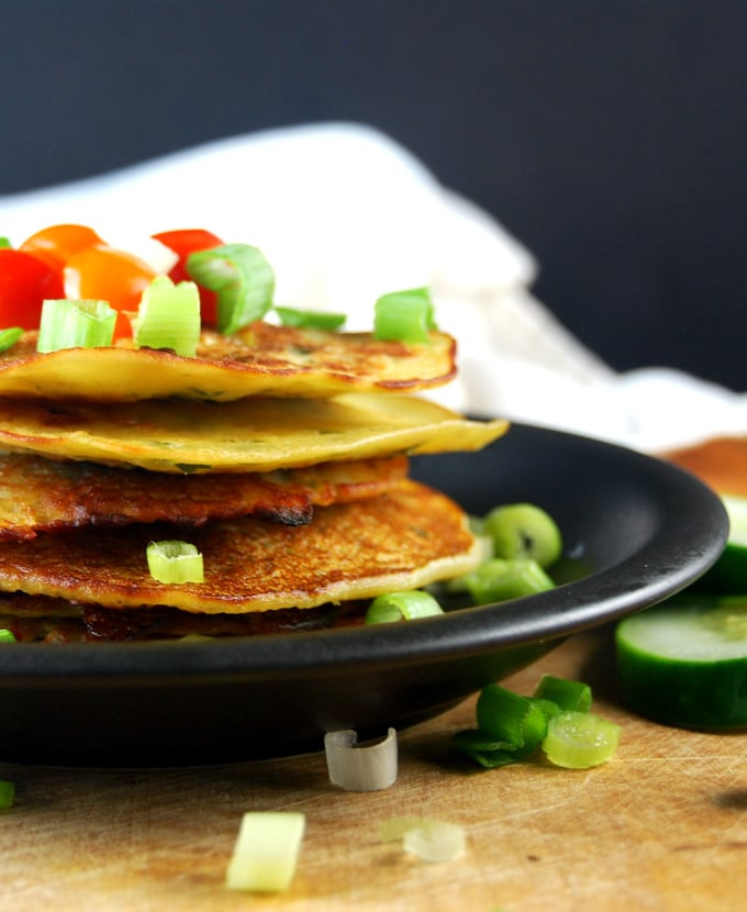 Partial shot of Savory Cucumber Pancakes on a black plate with scallions and cherry tomatoes and cucumber slices.
