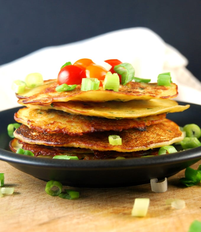 Closeup of Savory Cucumber Pancakes on a black plate with scallions and tomatoes.