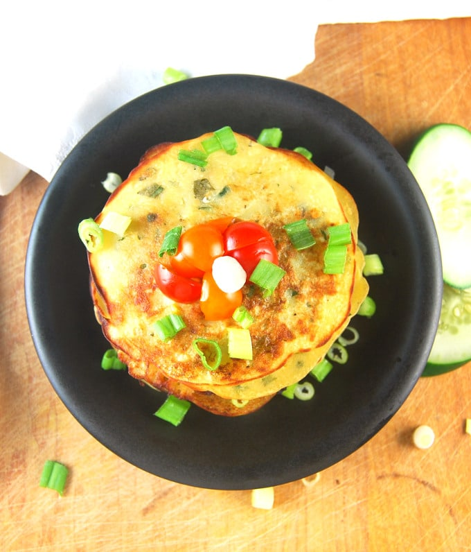 Overhead photo of Savory Cucumber Pancakes on a black plate with scallions, cherry tomatoes and cucumbers.