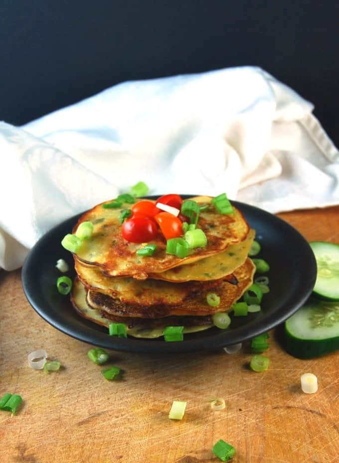Savory Vegan Cucumber Pancakes on a black plate with scallions and cherry tomatoes