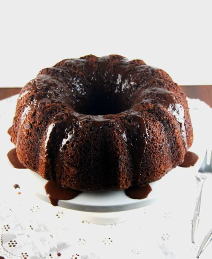 Vegan Chocolate Orange Bundt Cake with chocolate sauce on a white cake stand on a lace tablecloth
