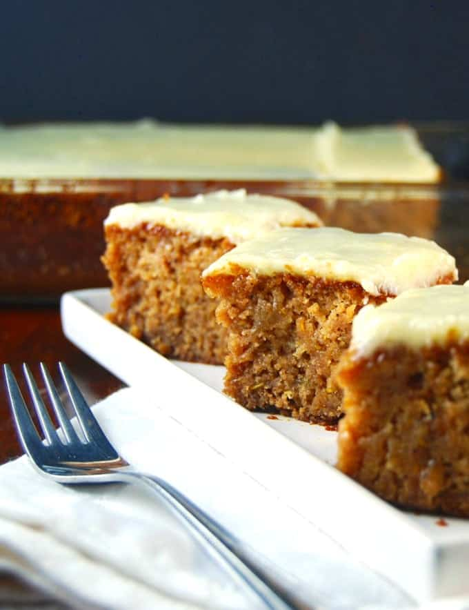 Squares of vegan Squash Cake with Pineapple Frosting arranged in a white rectangular plate.