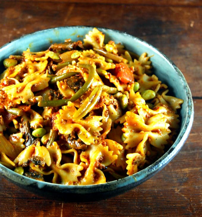 Front shot of glazed bowl with vegan Farfalle with Chorizo and Greens.