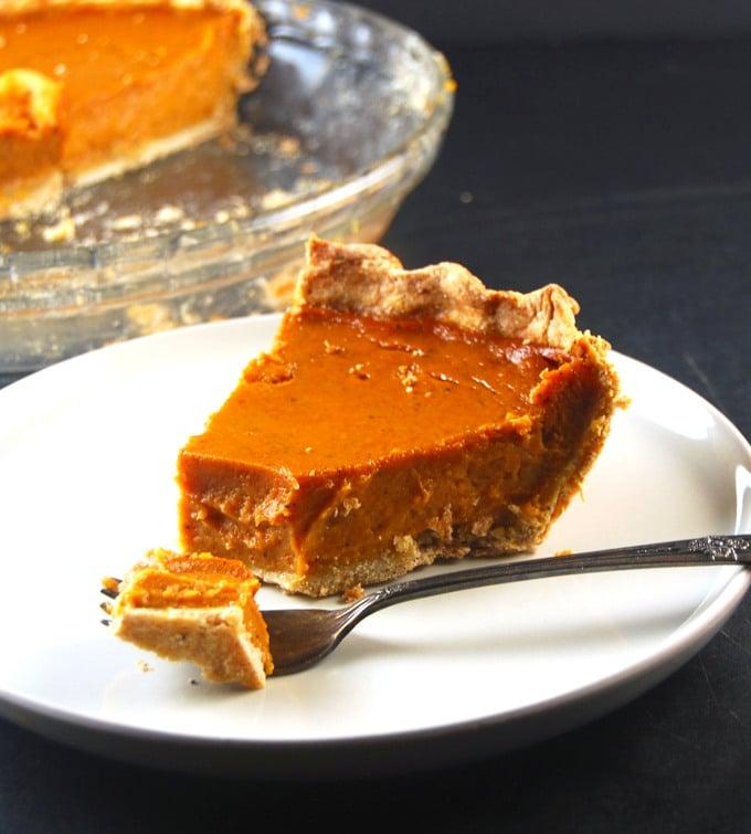 Photo of a slice of vegan pumpkin pie with a wholegrain crust.