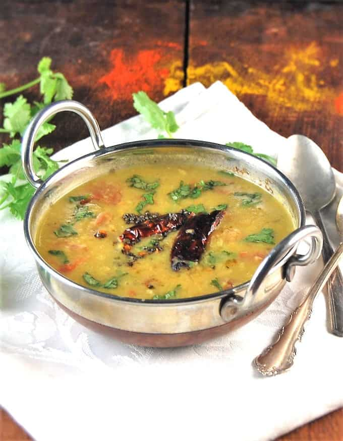 Photo of Dal Tadka in a kadhai bowl with spices and cilantro scattered around and a tadka of mustard seeds and red chile peppers.