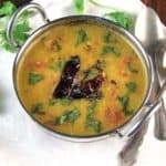 Dal Tarka in a karahi bowl with a garnish of cilantro and red chili peppers