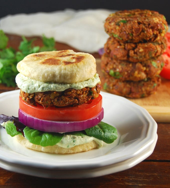 """Photo of Tandoori Naan Burger with naan """"buns"""" on two white plates with more burger patties in the background."""
