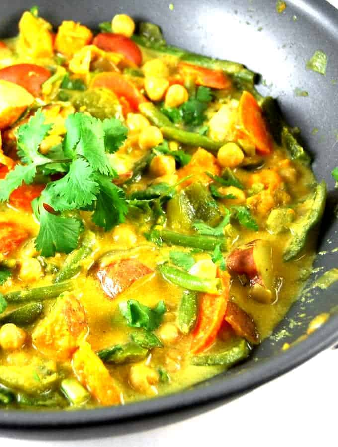A tight closeup shot of creamy vegetable curry with carrots, green beans, potatoes and sweet potatoes in a sea of coconut milk with curry powder and other spices and a garnish of cilantro.