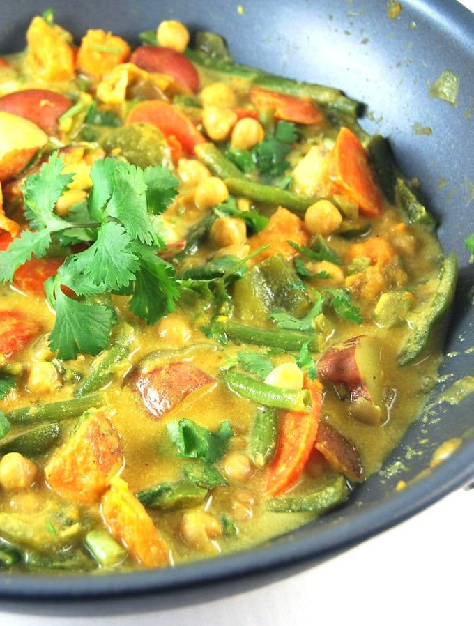 Vegetable Curry in a wok with sweet potatoes, carrots, green beans, potatoes and cilantro