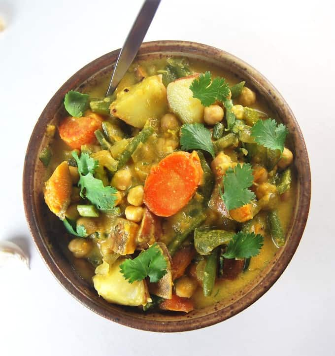 A bowl of vegetable curry with carrots, potatoes, sweet potatoes, green beans and chickpeas