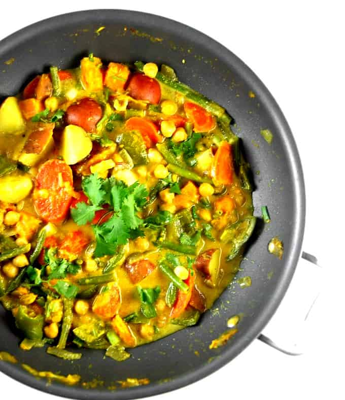 An overheads shot of a wok with creamy vegetable curry with carrots, green beans, potatoes and sweet potatoes in a sea of coconut milk with curry powder and other spices and a garnish of cilantro.