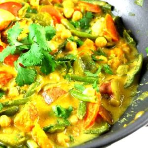 Closeup of vegetable curry in a wok with mixed veggies and cilantro