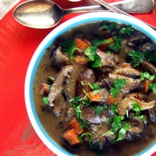 A partial overhead shot of vegan osso buco with savory wild mushrooms in an herby sauce with carrots and parsley on a red background with silver spoons next to the bowl.
