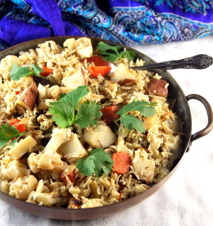 Pressure Cooker Vegetable Biryani served in a copper pan with spoon.