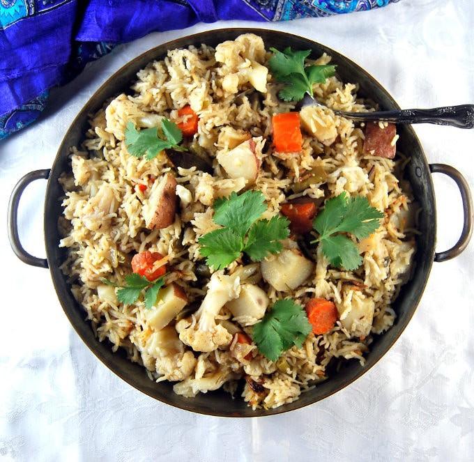 Pressure Cooker Vegetable Biryani in a copper pan with spoon.