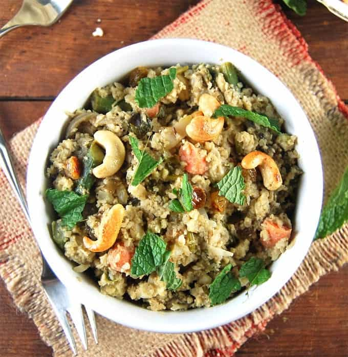 Overhead photo of Cauliflower Rice Biryani with mint leaves and cashews in a white bowl on a burlap fabric.