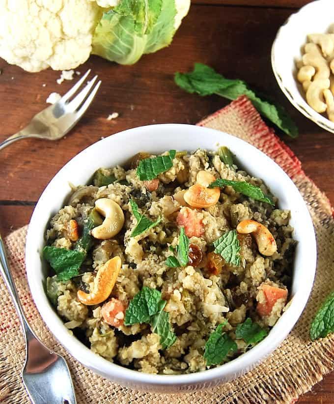 Cauliflower Rice Biryani in a white bowl with mint and cashews.