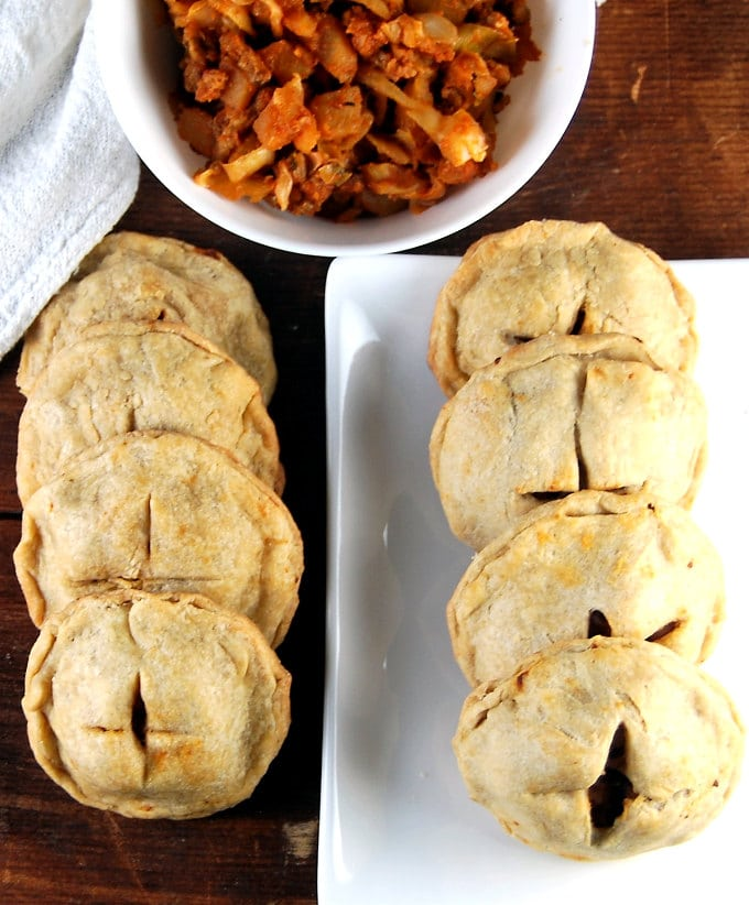 Vegan Irish Hand Pies on a table and plate with stuffing.