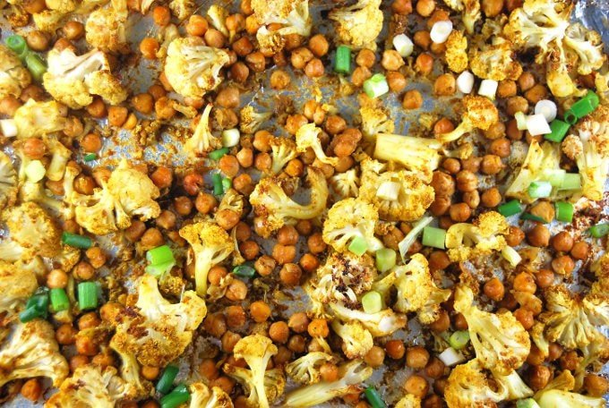 Close-up shot of cauliflower and chickpeas on a sheet pan