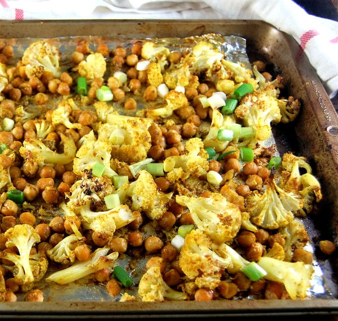 Cauliflower and chickpeas roasting with Indian spices on a sheet pan