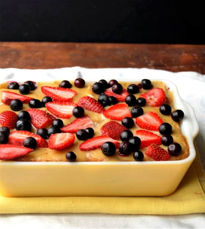 Photo of a colorful, berry-studded Vegan PB&J Bread Pudding in a yellow and white baking dish.