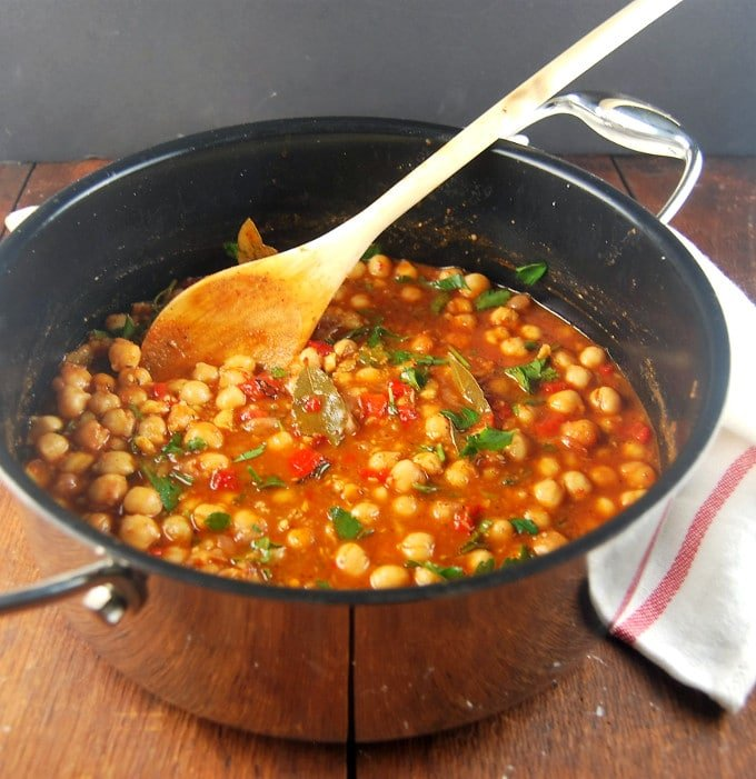 Lebanese Chickpea Stew in a pot with a wooden ladle and napkin.