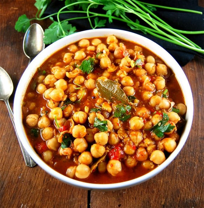 Lebanese Chickpea Stew in a white bowl with spoons.