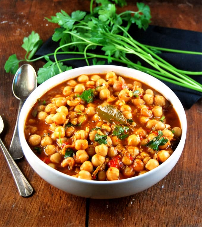Lebanese Chickpea Stew in a white ceramic bowl with silver spoons.
