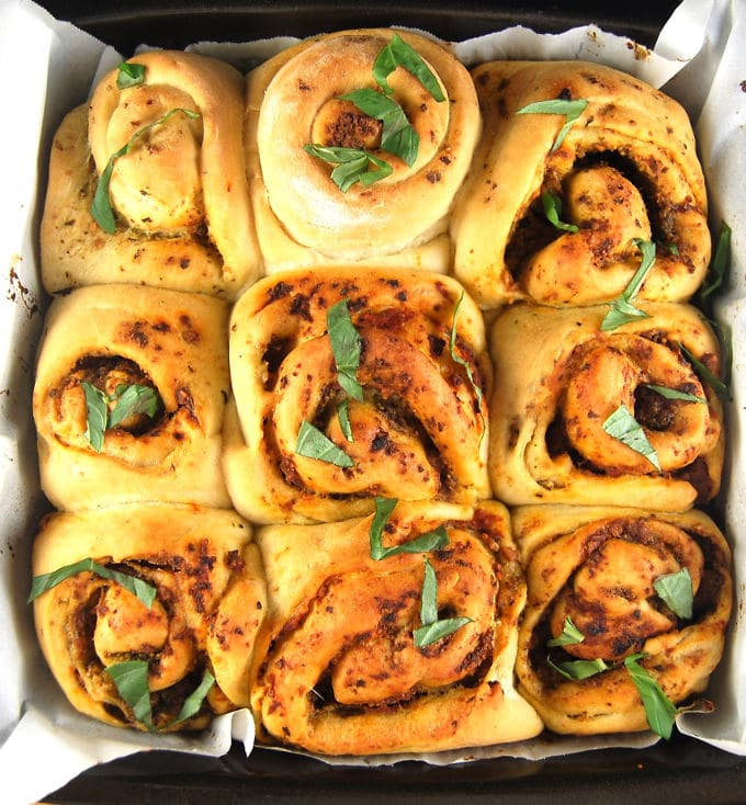Fresh baked vegan pizza rolls in a square baking pan with parsley scattered on top