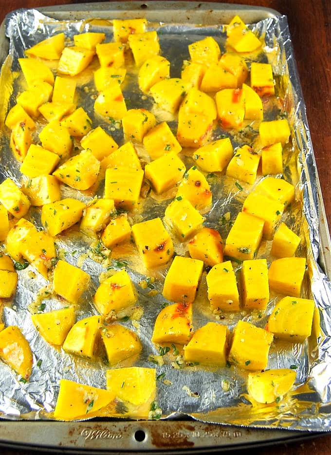 Roasted Golden Beets with Rosemary and Garlic on a baking sheet lined with aluminum foil, waiting to go into the oven.