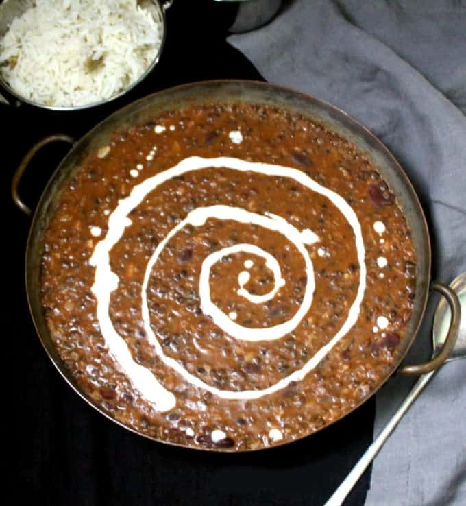 Top shot of a copper serving dish with creamy and buttery dal makhani with coconot cream swirled through it. In the background are cumin rice, slices of onion and lemon, and a gray napkin on a black background.