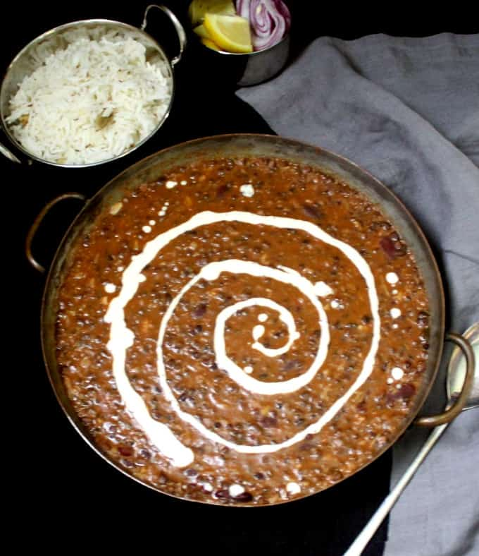 A copper serving dish with creamy and buttery dal makhani with coconot cream swirled through it. In the background are cumin rice, slices of onion and lemon, and a gray napkin on a black background.