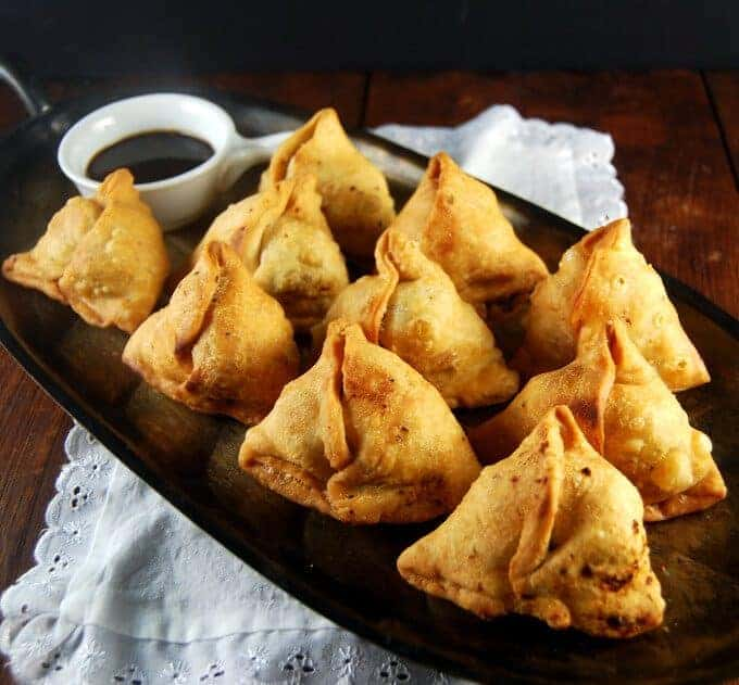 A silver tray with 10 flaky, golden Indian Punjabi samosas and tamarind chutney in a white cup, sitting on a white lace napkin