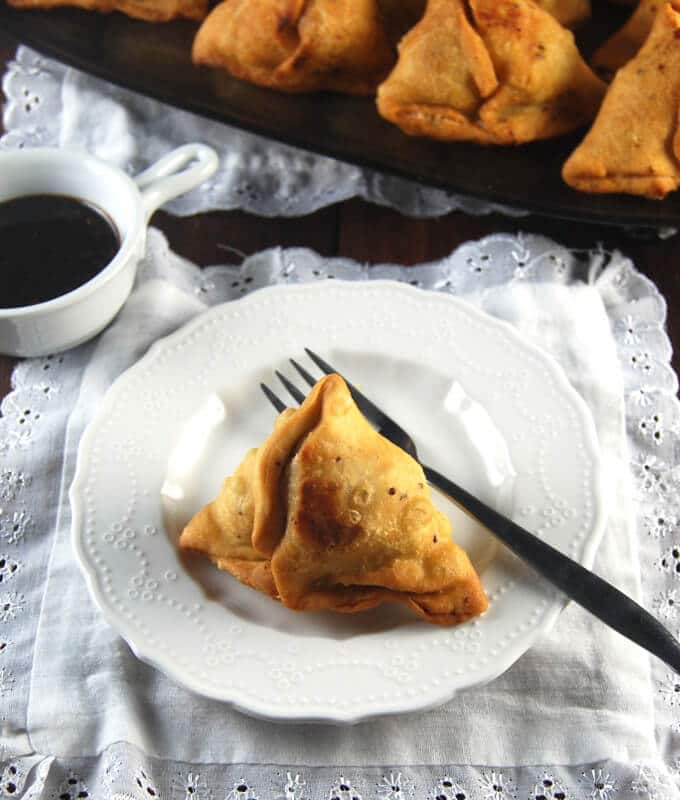 Photo of a single samosa on a plate with a fork on a white lace-bordered napkin with tamarind date chutney on the side.