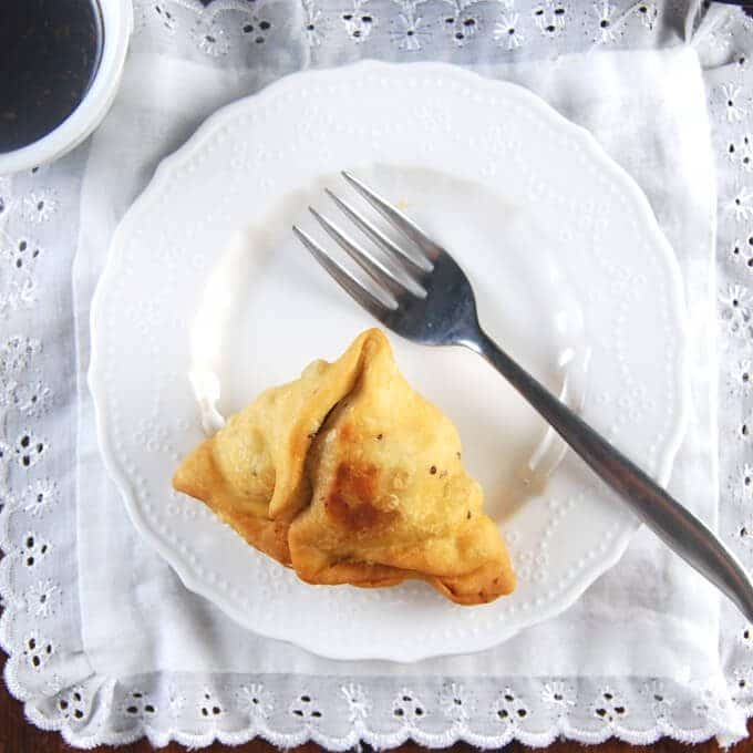 A single samosa in a white plate with a fork and a white napkin
