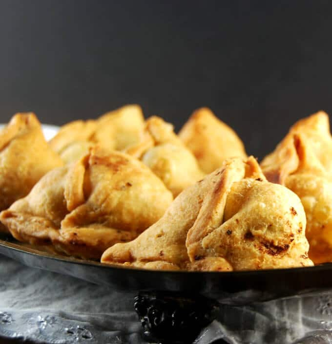 Front shot of perfect restaurant-style samosas with flaky golden wrappers and stuffed with potatoes and peas.