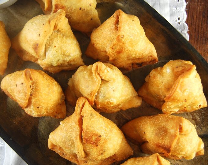 Close-up shot of seven golden samosas on a tray