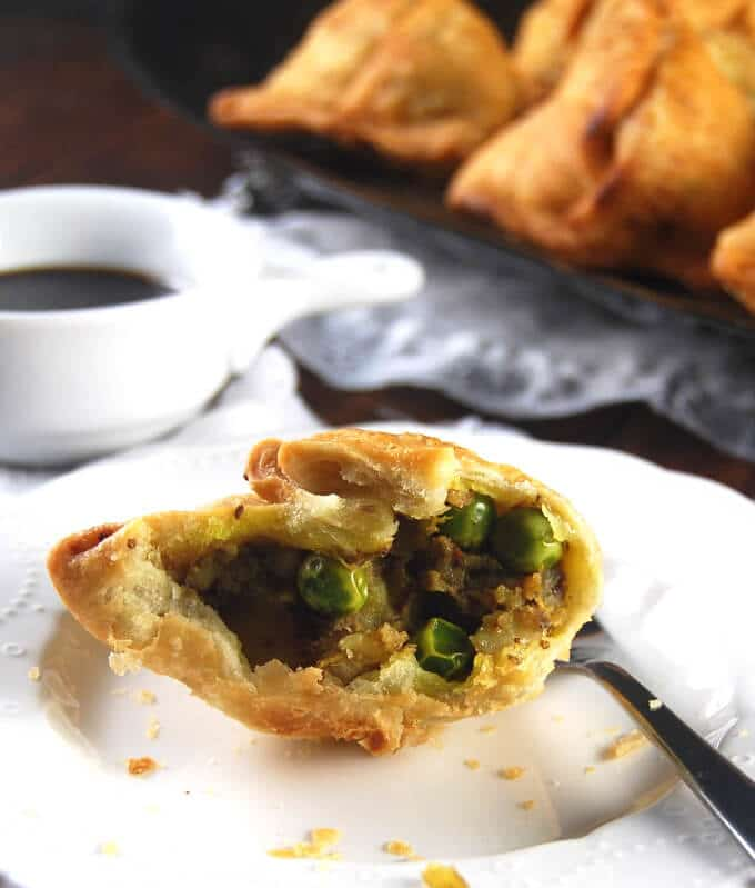 An opened samosa showing the spicy potatoes and peas filling inside and the flaky wrapper, on a white plate with a fork and chutney on the side.